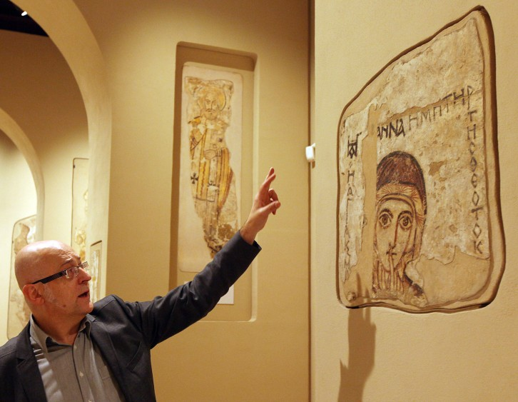 A man points at a 9th century wall painting of Saint Anna