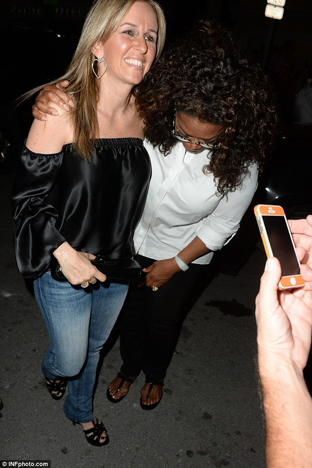 Are you okay? Oprah Winfrey gets out of her car to check a woman's foot after her driver accidentally ran over her high heel on Saturday night