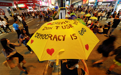 A woman sits under a yellow umbrella as pro-democracy protesters gather on a main street they occupy at Mongkok shopping district in Hong Kong