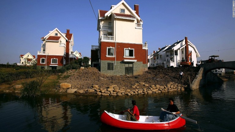 Two men row past houses built in a northern European style at the Luodian development in Huangzho, China.