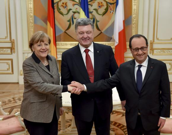 Ukraine's President Poroshenko shakes hands with German Chancellor Merkel and French President Hollande during their meeting in Kiev